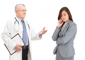 Mature doctor talking to a worried male patient, isolated on whi